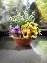 Gravdekoration med petunior, violer och liljekonvaljer
